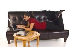 Mujer de negocios con la computadora portátil en el sofá Imagen de archivo libre de regalías