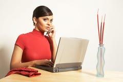 Mujer de negocios con la computadora portátil y el teléfono Fotografía de archivo