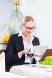 Mujer de negocios con la tableta en restaurante Imagen de archivo