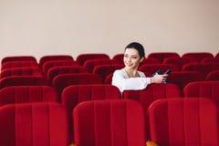 mujer de negocios con los documentos y teléfono que se sienta en la silla del asiento imagen de archivo libre de regalías