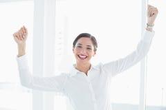 Mujer de negocios con los puños apretados en la oficina Imagen de archivo libre de regalías