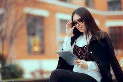 Mujer de negocios con los vidrios y Tablet PC de lectura afuera Imagen de archivo libre de regalías