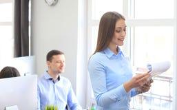Mujer de negocios con su personal, grupo de la gente en fondo en la oficina brillante moderna fotos de archivo libres de regalías