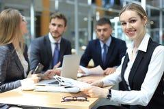 Mujer de negocios con su personal, grupo de la gente en fondo en la oficina brillante moderna dentro foto de archivo libre de regalías