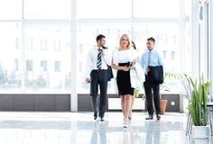 Mujer de negocios con sus colegas que se colocan en el pasillo de la oficina Imagen de archivo libre de regalías
