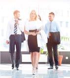 Mujer de negocios con sus colegas que se colocan en el pasillo de la oficina Fotos de archivo