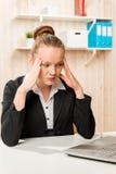Mujer de negocios con un dolor de cabeza que mira el ordenador portátil Fotografía de archivo