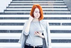 Mujer de negocios con una tableta en las manos que miran abajo en el fondo de las escaleras Imagen de archivo libre de regalías