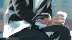 Mujer de negocios con una taza de café y de un teléfono móvil en las manos metrajes
