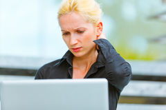 Mujer de negocios concentrada que usa la computadora portátil Imagenes de archivo