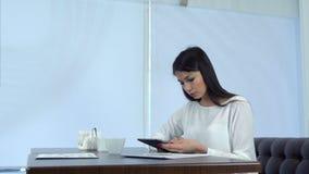 Mujer de negocios concentrada que usa la tableta digital en un café almacen de metraje de vídeo
