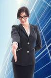 Mujer de negocios confiada que hace gesto que da la bienvenida Foto de archivo