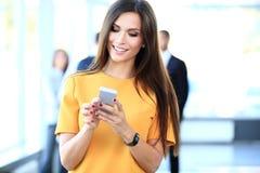 Mujer de negocios confiada sonriente que tiene una llamada de teléfono Imagen de archivo libre de regalías