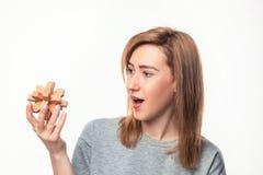 Mujer de negocios de 24 años atractiva que parece confundida con rompecabezas de madera Imágenes de archivo libres de regalías