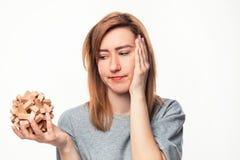 Mujer de negocios de 24 años atractiva que parece confundida con rompecabezas de madera Fotografía de archivo libre de regalías