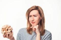Mujer de negocios de 24 años atractiva que parece confundida con rompecabezas de madera Imagen de archivo libre de regalías