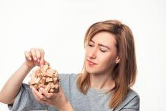 Mujer de negocios de 24 años atractiva que parece confundida con rompecabezas de madera Fotos de archivo libres de regalías