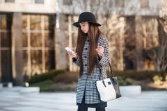 Mujer de negocios de Bauatiful que usa smartphone y caminando cerca del edificio de oficinas en la calle Imagen de archivo libre de regalías