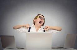 Mujer de negocios de bostezo que se sienta en el escritorio con los ordenadores fotografía de archivo libre de regalías