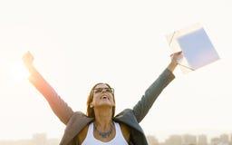 Mujer de negocios de la ciudad que celebra éxito en puesta del sol Imagen de archivo libre de regalías