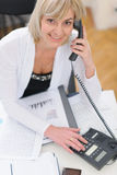 Mujer de negocios de la Edad Media que hace llamada de teléfono Imagen de archivo libre de regalías