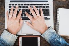 Mujer de negocios de la mañana Las manos femeninas están funcionando en un ordenador portátil, al lado del teléfono Marco horizon Fotos de archivo