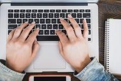 Mujer de negocios de la mañana Las manos femeninas están funcionando en un ordenador portátil, al lado del teléfono Marco horizon Foto de archivo libre de regalías