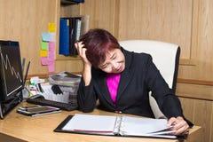 Mujer de negocios de la tensión que mira problema del trabajo de la hoja del documento en oficina Imagenes de archivo