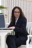 Mujer de negocios de Latina con los vidrios en la computadora portátil fotos de archivo