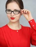 Mujer de negocios de moda con una camisa y un retrato rojos de los vidrios, sosteniendo las gafas de sol en su mano Imágenes de archivo libres de regalías