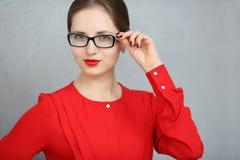 Mujer de negocios de moda con una camisa y un retrato rojos de los vidrios, sosteniendo los vidrios en su mano Foto de archivo libre de regalías