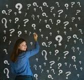 Mujer de negocios de pensamiento con los signos de interrogación de la tiza Imágenes de archivo libres de regalías