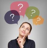 Mujer de negocios de pensamiento con muchas preguntas imagenes de archivo