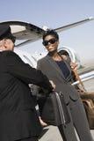 Mujer de negocios de Taking Briefcase From del conductor en el campo de aviación fotos de archivo libres de regalías