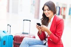 Mujer de negocios del aeropuerto en el teléfono elegante en la puerta foto de archivo
