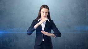 Mujer de negocios del retrato del primer que aumenta las manos en el ataque aéreo con la tajada del karate, fondo azul aislado Fotos de archivo