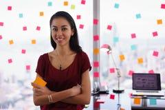 Mujer de negocios del retrato que escribe las notas pegajosas que sonríen en la cámara imagenes de archivo