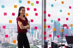 Mujer de negocios del retrato que muerde a Pen Writing Sticky Notes imagen de archivo