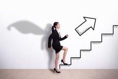 Mujer de negocios del super héroe con la escalera Fotografía de archivo