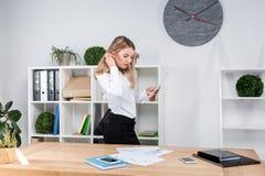 Mujer de negocios del tema en el trabajo Situación de trabajo caucásica joven hermosa en la oficina cerca de la tabla, controles  fotografía de archivo libre de regalías