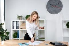Mujer de negocios del tema en el trabajo Situación de trabajo caucásica joven hermosa en la oficina cerca de la tabla, controles  imágenes de archivo libres de regalías
