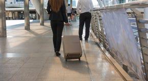 Mujer de negocios del viaje que tira del bolso de la maleta que camina adelante en Imagenes de archivo