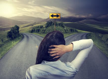 Mujer de negocios delante de dos caminos que piensa la decisión Foto de archivo libre de regalías