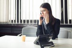 Mujer de negocios deprimida subrayada preocupante del oficinista que recibe llamada de teléfono de la emergencia de las malas not Fotografía de archivo