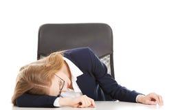 Mujer de negocios durmiente por la tabla. Foto de archivo