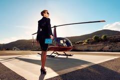 Mujer de negocios elegante cerca del helicóptero imagen de archivo