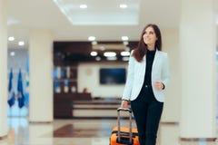 Mujer de negocios elegante con equipaje de la carretilla del viaje en pasillo del hotel imagenes de archivo