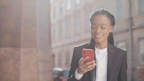 Mujer de negocios elegante del Afro que envía el mensaje audio de la voz en el teléfono móvil en hablar al aire libre con el ayud almacen de video