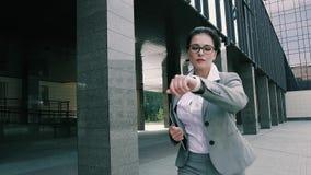 Mujer de negocios elegante que camina hacia el edificio de oficinas metrajes