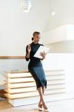 Mujer de negocios elegante severa que lleva el vestido negro y los zapatos beige en la oficina ligera que mira su orden del día,  Fotografía de archivo libre de regalías